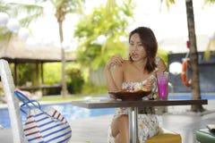 Glückliche Asiatin auf ihrem 20s gesundes Lebensmittel für das Brunchfrühstück oder -mittagessen genießend, die an der Kaffeestub Stockfotos