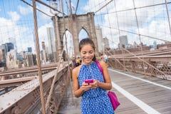 Glückliche Asiatin, die das Telefon simst auf Brooklyn-Brücke, New York verwendet Stockfotografie