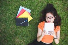 Glückliche Asiatin, die Tablette bei der Entspannung im Park verwendet Leute und lizenzfreie stockfotos