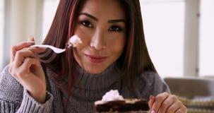 Glückliche Asiatin, die zu Hause mit Kuchen lächelt stockfoto