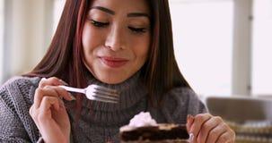 Glückliche Asiatin, die zu Hause mit Kuchen lächelt lizenzfreies stockbild
