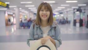 Glückliche Asiatin, die zur Kamera beim Bleiben am Anschluss im internationalen Flughafen, weibliches touristisches bereites, im  stock video footage