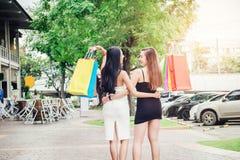 Glückliche Asiatinfreundschaft, die Einkaufstaschen herein ausgebend genießt Stockfotos