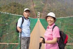 Glückliche asiatische ältere Paare, die herein auf die Brücke gehen Lizenzfreies Stockbild
