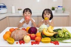 Glückliche asiatische chinesische kleine Schwestern, die Obst und Gemüse essen Stockbild