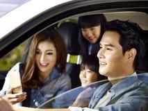 Glückliche asiatische Familie, die mit dem Auto reist Lizenzfreie Stockfotografie