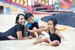 Glückliche asiatische Familie, die am Swimmingpool aufwirft Stockfotos