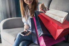 Glückliche asiatische Frau, die auf Sofa sitzt und intelligentes Telefon verwendet lizenzfreies stockbild