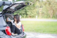 Glückliche asiatische Frau, die auf Stamm des Hecktürmodellautos im Park sitzt Lizenzfreies Stockbild