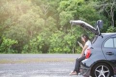 Glückliche asiatische Frau, die auf Stamm des Hecktürmodellautos im Park sitzt stockfoto