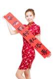 Glückliche asiatische Frau, die chinesische Frühlingsfestdistichons zeigt Stockfotos