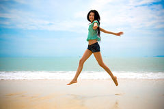 Glückliche asiatische Frau, die in die Luft am Strand geht Stockbilder