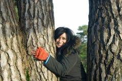 Glückliche asiatische Frau, die einen Baum umarmt Stockfoto