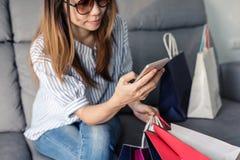 Glückliche asiatische Frau, die Kreditkarte und intelligentes Telefon hält lizenzfreie stockbilder