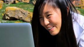 Glückliche asiatische Frau, die mit PC im Park plaudert stock video footage