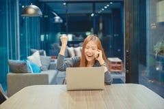 Glückliche asiatische Geschäftsfrau, die einen Laptop im Wohnzimmer an nah verwendet stockfotografie