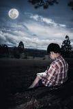 Glückliche asiatische Jungenzeichnung, im Freien am Park getrennte alte Bücher niedrig Stockfoto