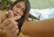 Glückliche asiatische koreanische touristische Frau, die Handy halten lächeln oder Kamera, die Selbstporträt selfie Foto draußen  stockbilder