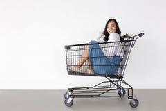 Glückliche asiatische Mädchenliebe, die mit Laufkatzeneinkaufswagen kauft lizenzfreie stockfotografie