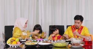 Glückliche asiatische moslemische Familie, die zu Abend isst stock video