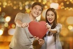 Glückliche asiatische Paare, die Büttenpapierherz halten Stockbilder