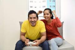 Glückliche asiatische Paare, die Videospiele spielen und Spaß haben stockfotos