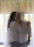 Glückliche asiatische Paare im weißen Hemd halten sich hinter dem Vorhang Lizenzfreie Stockfotografie