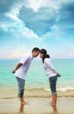 Glückliche asiatische Paare am Strand lizenzfreie stockfotos