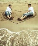 Glückliche asiatische Paare am Strand lizenzfreie stockbilder