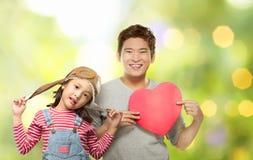 Glückliche asiatische Tochter und ihr Vater, die rotes Herz hält lizenzfreie stockfotos