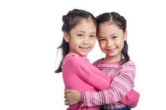 Glückliche asiatische Zwillingsschwesterumarmung stockfoto