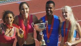 Glückliche Athleten, die stolz ihre Schalen und Medaillen, geehrte Preise demonstrieren stock video