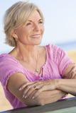 Glückliche attraktive ältere Frau, die draußen sitzt stockbild