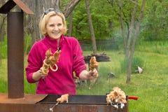 Glückliche attraktive blonde Frau, die auf einem BBQ kocht Stockfotografie