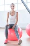 Glückliche attraktive Frau, die auf dem Ball sitzt Lizenzfreie Stockfotografie