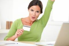 Glückliche attraktive Frau, die auf ihrem Schreibtisch froh schaut Stockbild