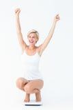Glückliche attraktive Frau, die auf Skalen sich duckt Lizenzfreies Stockbild