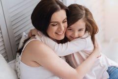 Glückliche attraktive Frau, die ihre Tochter umfasst Lizenzfreie Stockfotos