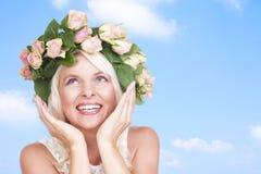 Glückliche attraktive Frau mit Blumen in ihrem Haar Lizenzfreies Stockfoto