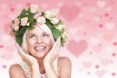 Glückliche attraktive Frau mit Blumen in ihrem Haar Stockfotos