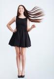 Glückliche attraktive Frau mit dem schönen langen dunklen Haar in der Bewegung Stockfotografie