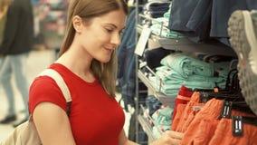 Glückliche attraktive Frau in rotem T-Shirt Einkaufen in kaufender Kleidung des Malls Verbraucherschutzbewegung shopaholism Konze stock footage
