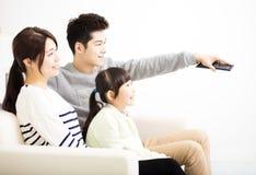 Glückliche attraktive junge Familie, die fernsieht stockbilder