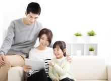 Glückliche attraktive junge Familie, welche die Tablette aufpasst lizenzfreie stockfotografie