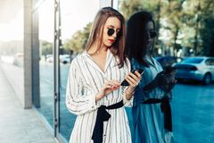 Glückliche attraktive junge Frau in der Sonnenbrille, die Smartphone betrachtet lizenzfreie stockfotos