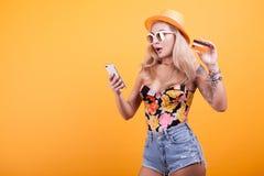Glückliche attraktive junge Frau, die Kreditkarte hält und zeigt Stockfoto