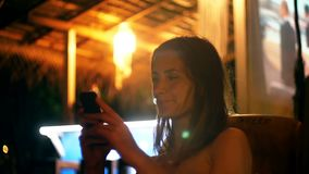 Glückliche attraktive junge Geschäftsfrau, die unter Verwendung Smartphone Einkaufsapp atmosphärische Nachtlounge bar-Café im im  stock video footage