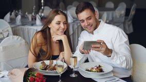 Glückliche attraktive junge Leute passen Smartphone zusammen auf, lächeln und sprechen beim Zu Abend essen im Restaurant stock video footage