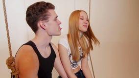 Glückliche attraktive junge Paare, die auf Schwingen lachen stock footage