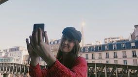 Glückliche attraktive lächelnde touristische Frau, die selfie Foto mit Eiffelturmansicht in Paris vom sonnigen Wohnungsbalkon mac stock video